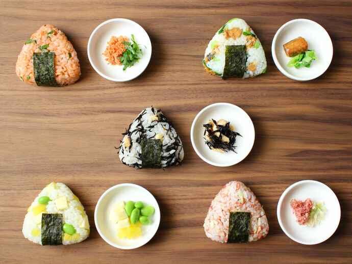 5種類のおにぎり。(左上から時計回りに)サケとシソ、サバ缶と小松菜、ヒジキと油揚げ、切り干し大根とコンビーフ、枝豆とたくあんとチーズ