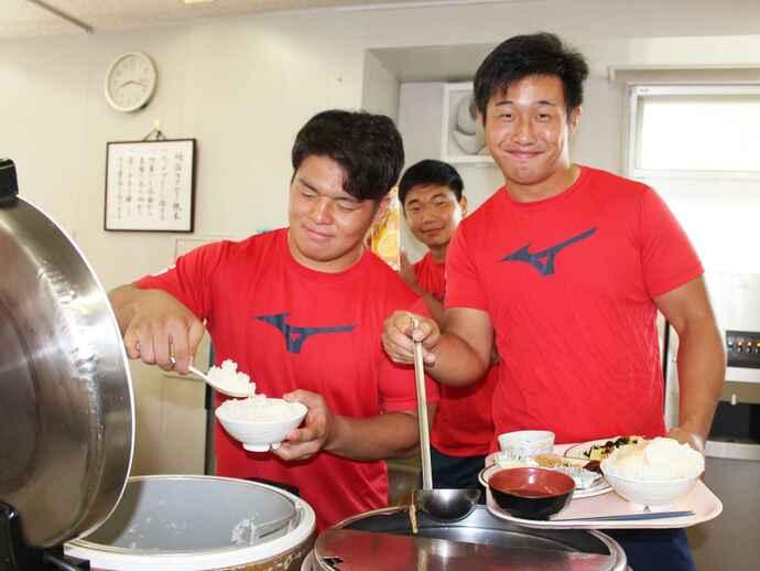 ご飯を盛る武井主将、辻選手。後方は安昌豪選手