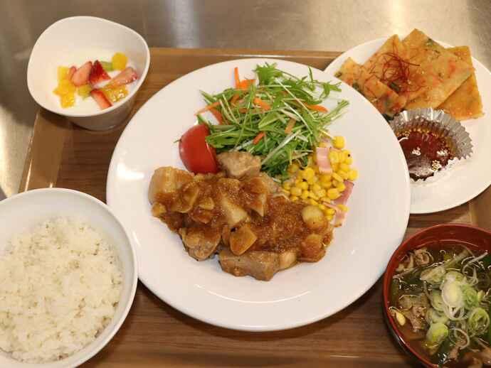 夕食メニュー。豚肩ロースのガリバタゴロゴロステーキ、海鮮チヂミ、テグタンスープ、フルーツヨーグルトなどが並ぶ