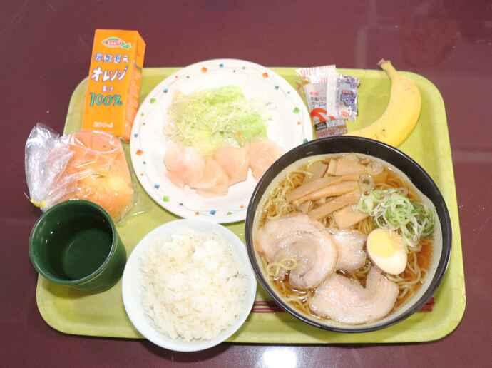 ある日の昼食。ラーメン、半ライス、水餃子、バナナ、パン、100%オレンジジュース