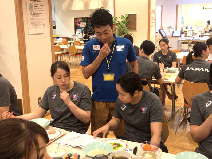 選手の食事の様子を見る上野氏(味の素VP提供)