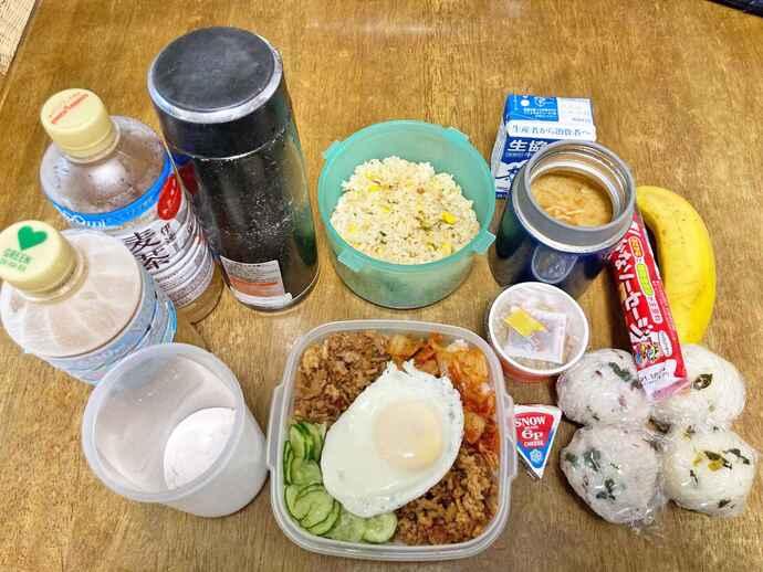 市和歌山・小園健太投手の平日の食事は色彩豊かで食欲も増す。真ん中上からチャーハン、みそ汁、納豆、牛乳は朝食セット。おにぎり玉4個と魚肉ソーセージ、バナナは補食。昼食は韓国風ピリ辛豚そぼろ丼でチーズも食べる。水筒、ペットボトル2本はすべて麦茶で、ペットボトル2本は凍らせることで保冷剤代わりの工夫。左下の粉末はサプリメント。細やかな栄養摂取を心掛ける(写真提供・母優佳さん)